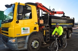 Cllr Bassam Mahfouz riding alongside an Ealing Council contractor vehicle fitted with the Cycle Safety Shield system